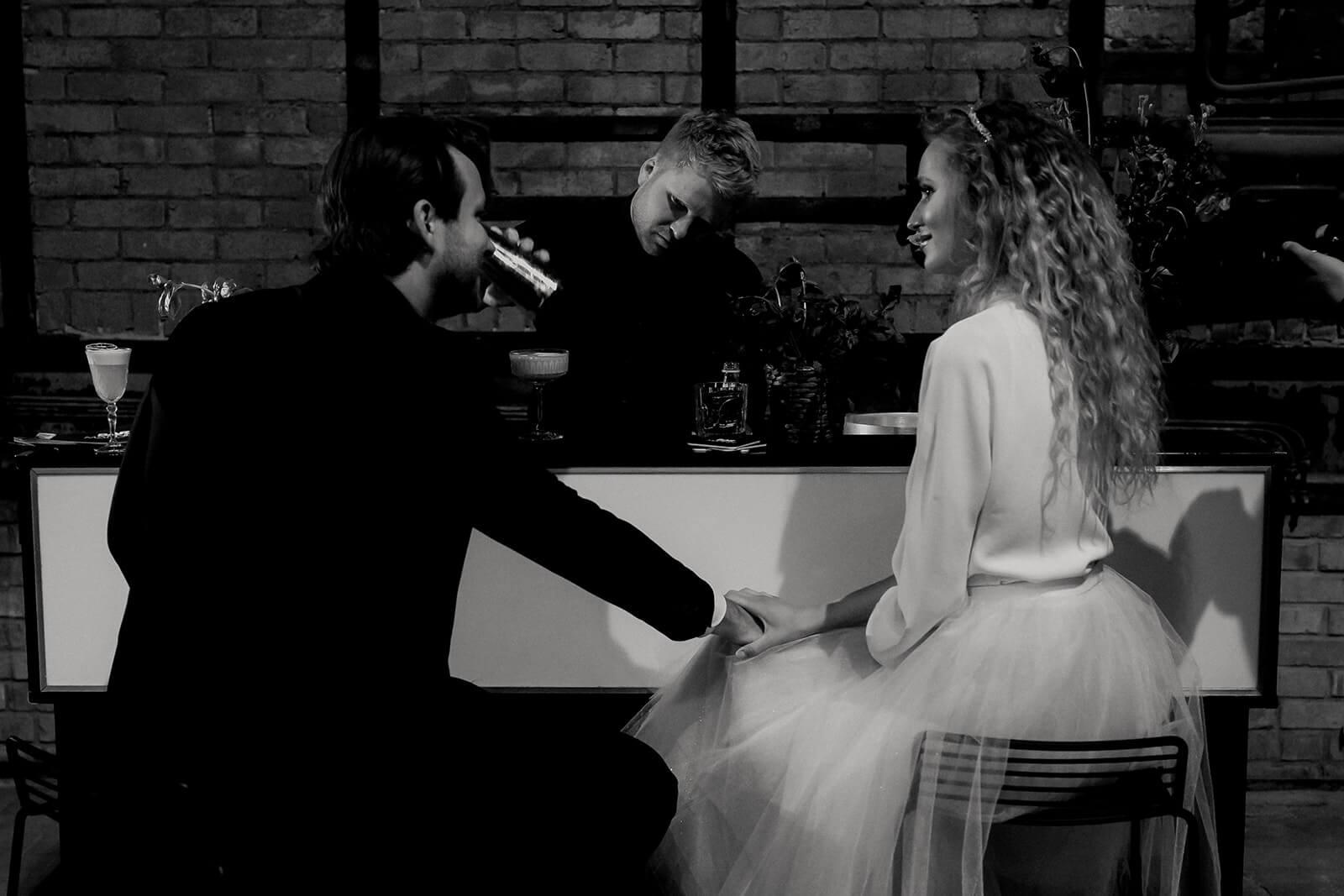 Brautpaar sitzt an der Bar mit Barkeeper - Hochzeitsdienstleister