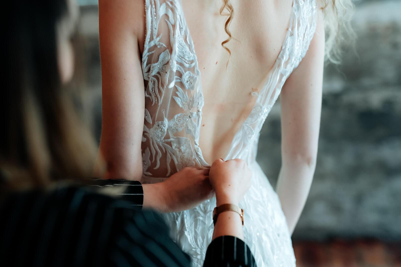 Hochzeitsplanerin hilft Braut ihr Kleid anzuziehen